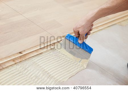 Close-up hand of handyman parquet carpenter worker adding glue on base during wood flooring