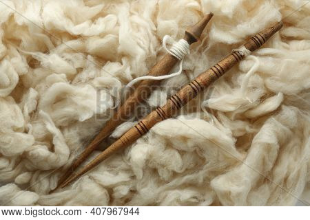 Soft White Wool With Spindles As Background, Top View