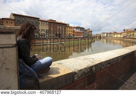 Pisa (pi), Italy - June 10, 2017: A Girl Messaging Near The Arno River, Pisa, Tuscany, Italy, Europe