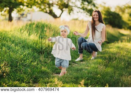Family Enjoying Life Together In The Summer Park. Happy Young Family Outdoors. Mother Is Playing Wit