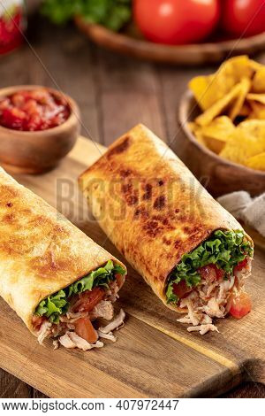 Chicken Burritos With Lettuce And Tomato On A Wooden Cutting Board With Tortilla Chips And Salsa In