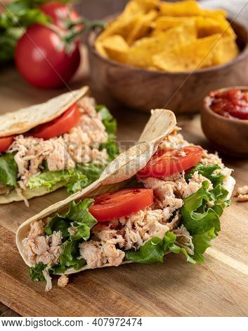 Chicken Taco With Lettuce And Tomato On A Wooden Cutting Board With Tortilla Chips And Salsa In Back
