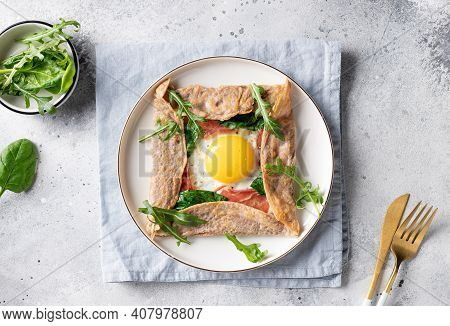 Homemade Buckwheat Crepe Galette With Egg, Ham And Spinach On Gray Background. Traditional French Di
