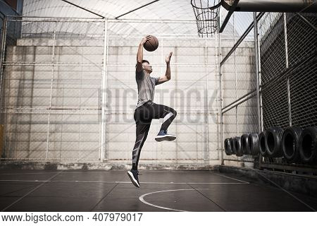 Young Asian Man Basketball Player Attempting A Dunk On Outdoor Court