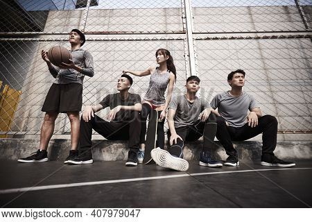 Group Of Five Asian Young Adults Men And Woman Resting Relaxing On Outdoor Basketball Court