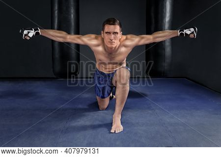 Muay Thai Fighter In Black Gloves And Blue Shorts Posing Against Two Punching Bags In The Gym. Profe