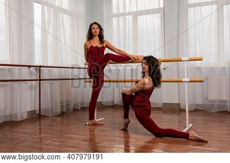 Two Young Womans Fitness Instructor In Red Sportswear Leggings And Top Stretching In The Gym Before