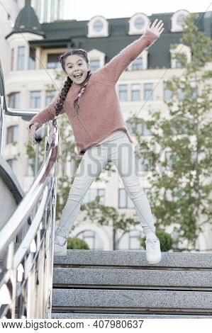 Running Down The Stairs. Happy Energetic Kid Jumping On Steps In Casual Wear. Energetic Little Girl