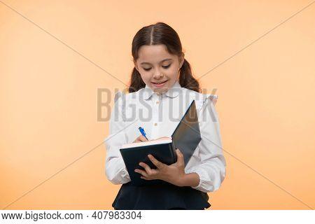 Schoolgirl Write In Notebook On Yellow Background. Girl In School Uniform, Back To School. Little Ch