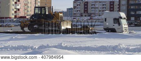 Kazakhstan, Ust-kamenogorsk,  February 21, 2020: Yellow Heavy Duty Crawler Bulldozer On Truck Traile