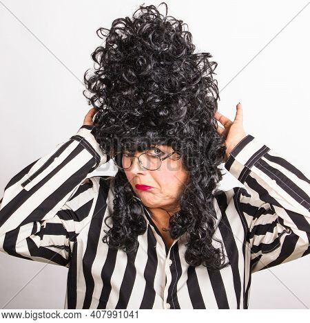 Adult Mature Woman In A Black High Wig, Black And White Striped Shirt On A White Background. Wrinkle