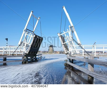 People Skate Through Drawbridge In Kinderdijk On Frozen Water Of Canal On Sunny Winter Day In The Ne