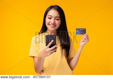 Happy Young Woman Using Mobile Phone Showing Plastic Credit Card Standing Over Yellow Background, On