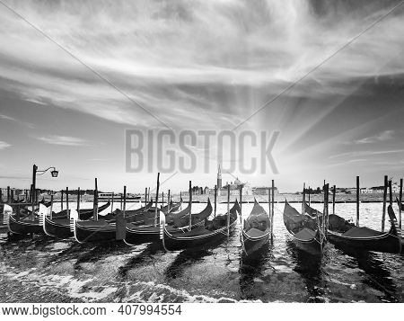 Grayscale. Parked Gondolas On Piazza San Marco And The Doge's Palace Embankment And Sunset Sunshine