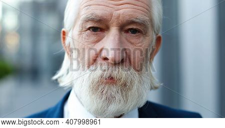 Portrait Of Caucasian Old Gray-haired Man Standing Outside And Looking At Camera With Sad Eyes. Sadn