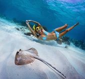 Underwater shoot of a woman swimming over sandy sea bottom with spotted ray on the foreground poster