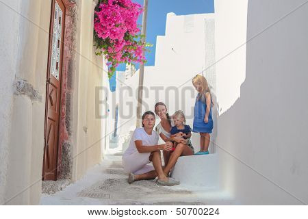 Beautiful Family Of Four Sitting On Doorstep At Old Greek House In The Street Emporio,santorini