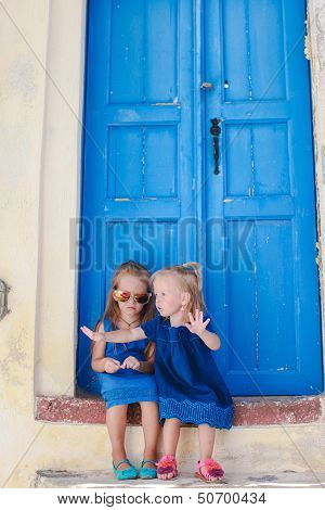 Little Adorable Girls Sitting Near Old Blue Door In Greek Village Of Emporio, Santorini