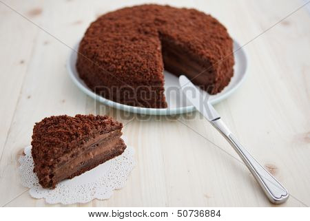 Homemade chocolate blackout cake with a cut piece on a wooden table