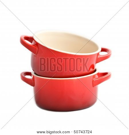 Two red cocottes (small casserole) without covers on a white background