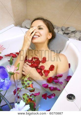 Happy Woman In A Bath With Rose-petals