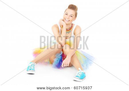 A picture of a happy woman sitting in a colorful skirt over white background