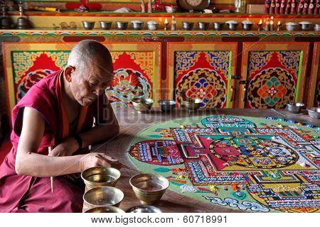 LADAKH, INDIA - SEPTEMBER 03, 2011: Buddhist monks making sand mandala in Diskit gompa at Nubra valley. Mandala - is a spiritual and ritual symbol in Hinduism and Buddhism, representing the Universe.