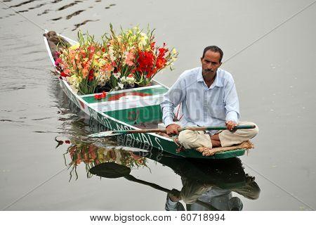 SRINAGAR, JAMMU AND KASHMIR, INDIA - JULY 20, 2006: Flower seller on Dal Lake in Srinagar rowing his floating flower shop