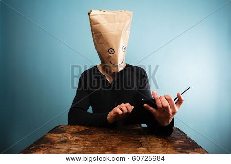 Man With Bag Over Head Using Tablet Computer