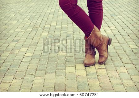 Young Girl Stands In The Shoes Crosslegged
