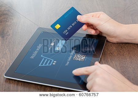 Female Hands Holding Credit Card And A Tablet In The Office And Making A Purchase Onlain