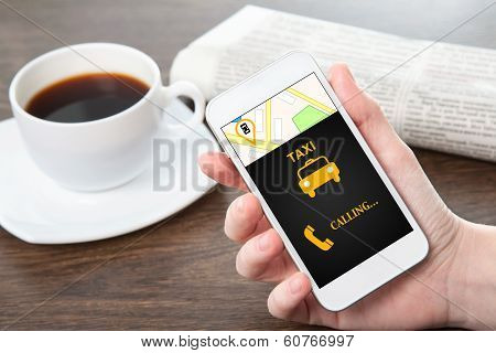 Businesswoman Hand Holding A Phone With Interface Taxi In The Office