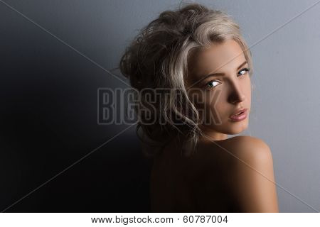 Shot of a sexy woman in black lingerie over dark background. poster