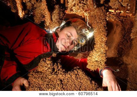 Spelunker admiring beautiful stalactites in a cave poster