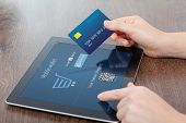 female hands holding credit card and a computer tablet on the table in the office and making a purchase onlain poster