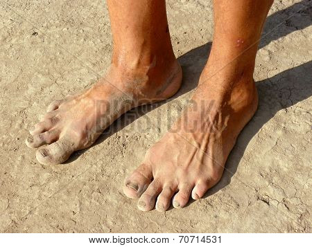 dirty male feet on dried earth