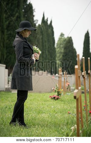 Young woman standing at graveside