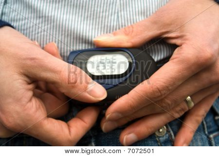 A Pedometer With Woman's Hands