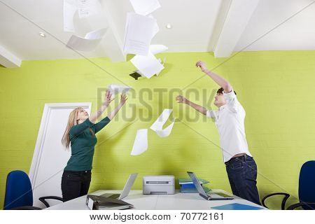 Side view of young businesspeople throwing documents in office