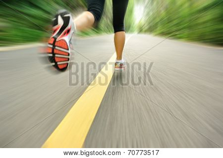 fitness woman legs running at forest