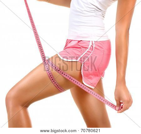 Fitness sporty woman measuring her hip with a measuring tape. Young Beautiful Girl Woman her Leg with a Metric Tape measure. Standing Sideways. Girl measures her thigh Measuring after weight loss. poster
