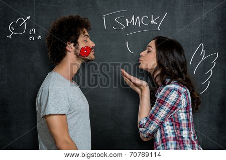 Woman Giving Flying Kiss To Her Boyfriend With Lip Sign On Cheek Over Gray Background