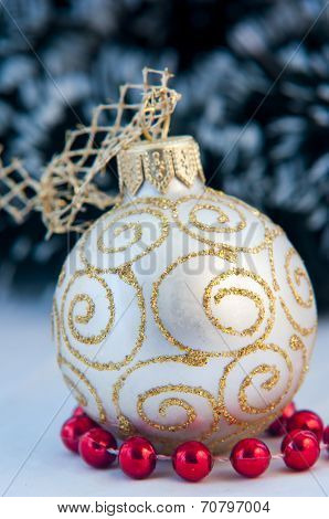 white Christmas decoration sitting on small red docorative balls