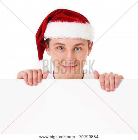 Happy smiling young man in Santa Claus hat showing blank signboard, isolated on white background