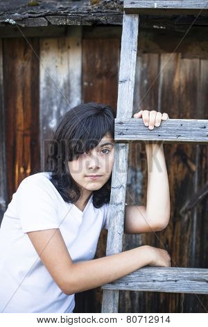 Black-haired teen girl with expressive eyes, a portrait in the countryside. Emo.