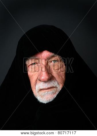 Elder Arab Sheik with a somber expression with a black headdress looking directly into the camera