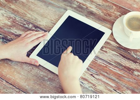 technology, internet and home concept - close up of female pointing finger to black blank tablet pc computer screen