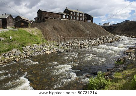 Traditional timber buildings of the copper smelter factory at the bank of Roa river in copper mines town of Roros, Norway. Roros town is declared a UNESCO WORLD Heritage site. poster