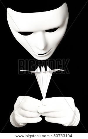 White theatrical mask and paper origami isolated on black