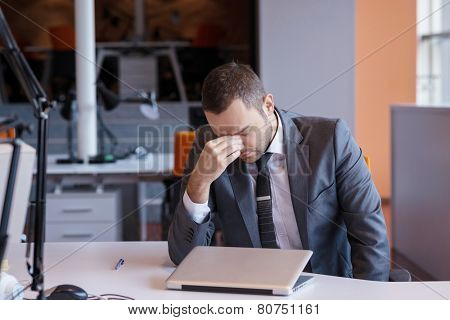 frustrated young business man working on laptop computer at office poster